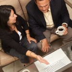 Man and Woman Working at Home Using Laptop with Coffee