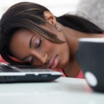 Young women sleeping with her head on a laptop